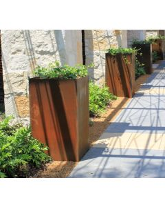 Four weathered Cor-Ten steel planters evenly spaced along a stone driveway.