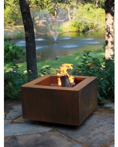 30 inch square Cor-ten steel fire pit with natural logs burning in the fire bowl.