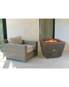 Weathered Cor-Ten steel pyramid fire pit with red fire glass in fire bowl with flames in fire bowl.  On off key valve is in the middle of the side of the fire pit.
