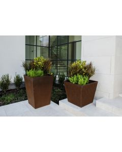 Two pyramid shaped Cor-Ten planters with a variety of plants.  Planters are sitting on limestone patio side by side.