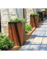 Four 35 inch tall columnar Cor-ten planters in a row along a stone walkway..