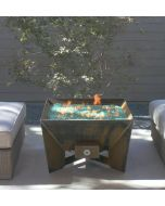 8 Gauge Cor-Ten steel DeZen Fire pit with green quarter inch fire glass in fire bowl.  The fire pit is turned on.